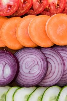Full frame di pomodori; carota; sfondo di fette di cipolla e cetriolo