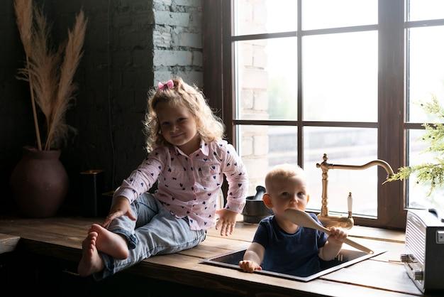 Full shot bambino con baby sitter nel lavandino
