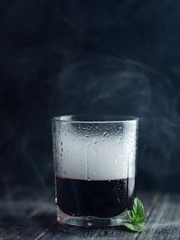 Fuma in un bicchiere con alcool rosso