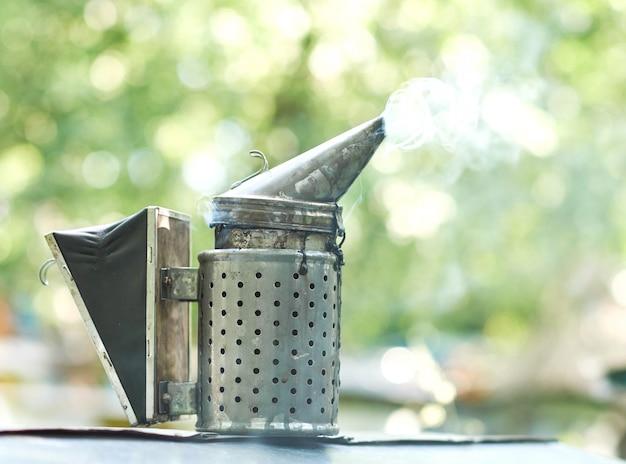 Fumatore dell'ape con il concetto professionale dello strumento di tecnologia dell'attrezzatura di apicoltura dell'apicoltura del copyspace del fumo.
