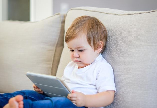 Fumetto di sorveglianza del piccolo bambino sveglio sulla compressa digitale che si siede sul sofà.
