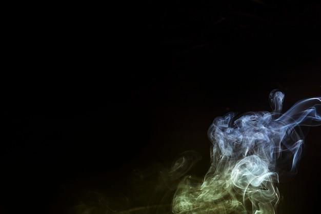 Fumo bianco e giallo all'angolo dello sfondo nero