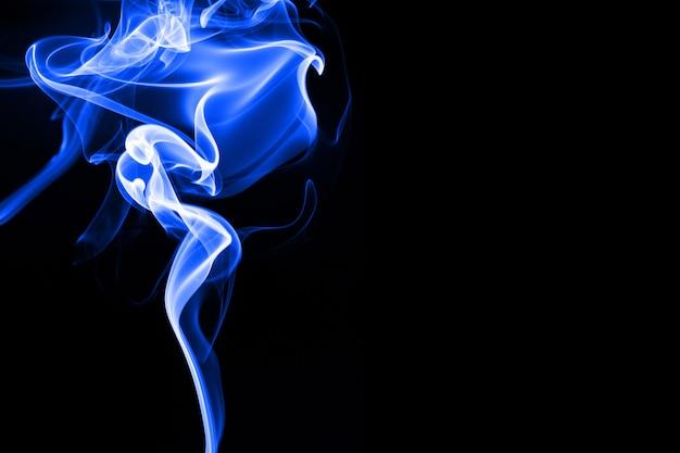 Fumo blu su sfondo nero, movimento astratto, concetto di oscurità