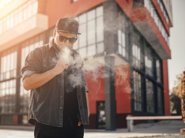 Fumo di giovane uomo bello con vape in posizione urbana