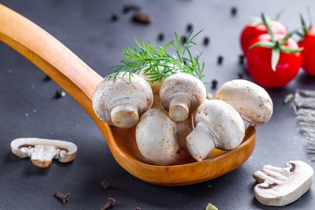 Funghi bianchi in cucchiaio di legno con aneto. cucinare piatti fatti in casa di pomodori ciliegia e champignon freschi maturi