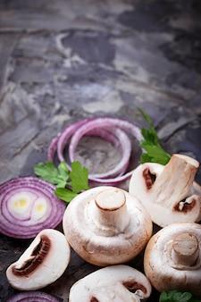 Funghi champignon freschi e cipolla rossa. messa a fuoco selettiva