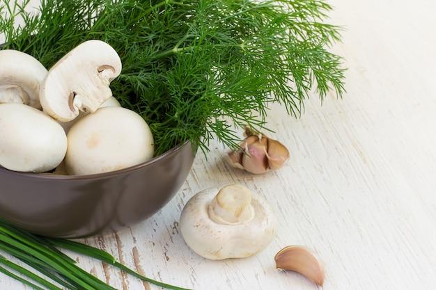 Funghi champignon in una ciotola con erbe fresche