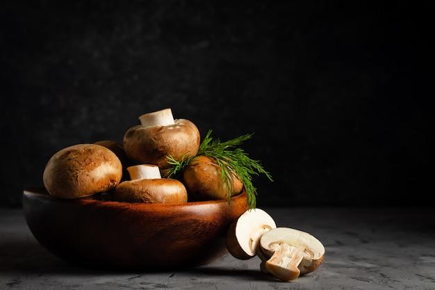 Funghi champignon marroni con aneto in un piatto di legno in chiave bassa