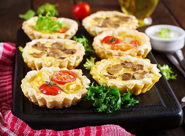 Funghi, cheddar, tortine di pomodori su legno
