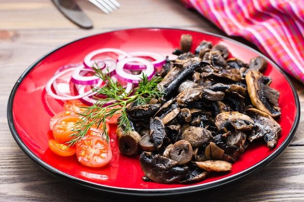 Funghi fritti, cipolla e pomodorini su un piatto su un tavolo di legno