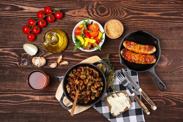 Funghi fritti e salsiccia in padella di ferro. ingredienti per il cibo semplice rustico, vista dall'alto.