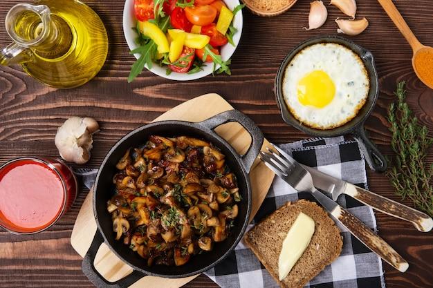 Funghi fritti e uova in padella di ferro. ingredienti per il cibo semplice rustico, vista dall'alto.