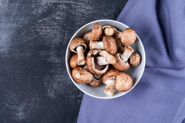 Funghi in una ciotola sul panno viola su una tabella scura