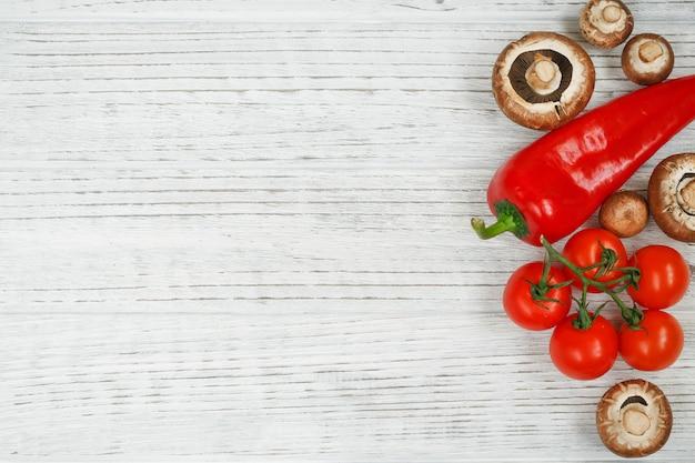 Funghi, pomodori, pepe su un tavolo in legno