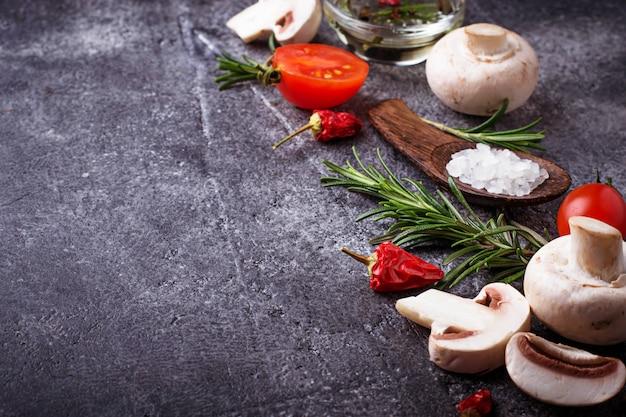 Funghi, pomodori, rosmarino, sale e olio. sfondo di cibo messa a fuoco selettiva