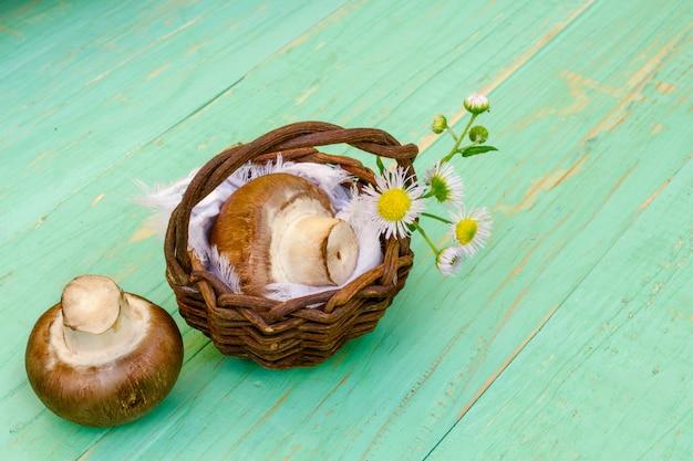 Funghi prataioli e cestino di vimini con un fiore di campo.