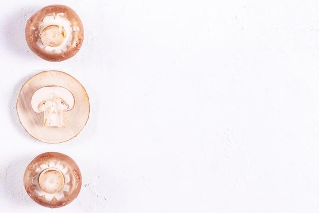 Funghi prataioli marroni su un supporto di legno su uno spazio bianco della copia del fondo