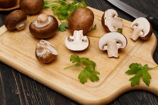 Funghi prataioli reali reali tagliati con verde sul bordo di legno.