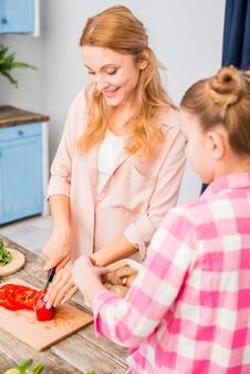 Fungo della holding della ragazza a disposizione che esamina sua madre che taglia il peperone dolce con la lama sulla tabella