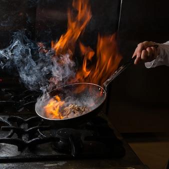 Fungo di vista laterale che frigge con fumo e fuoco e mano umana in pentola