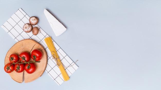 Fungo; pomodori rossi; pasta di formaggio e spaghetti con tovagliolo su sfondo grigio