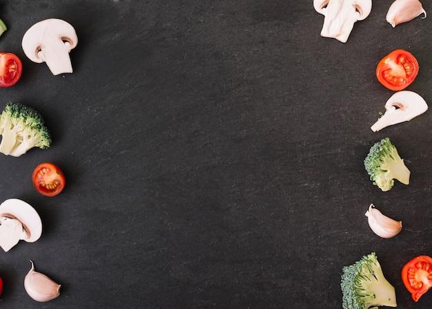 Fungo; pomodori; spicchi di aglio e broccoli su sfondo nero con spazio per scrivere il testo