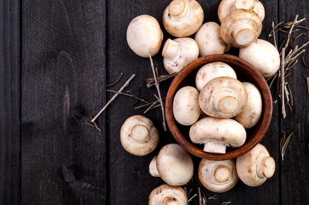Fungo prataiolo bianco fresco dei funghi in ciotola su fondo di legno scuro.
