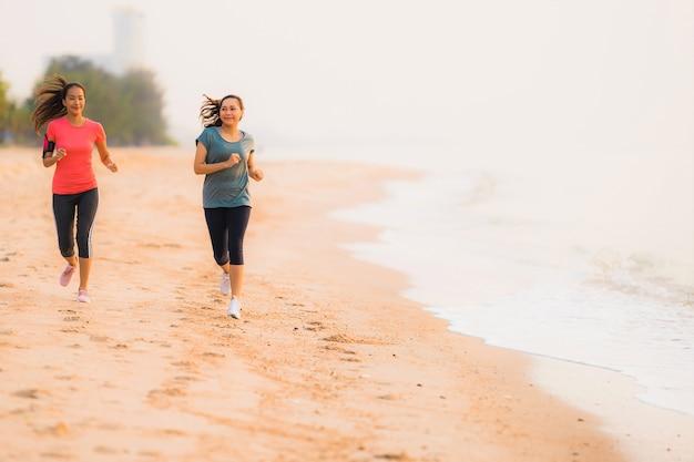Funzionamento asiatico della bella donna di sport del giovane ritratto ed esercizio sulla spiaggia vicino al mare ed oceano ad alba o tempo di tramonto