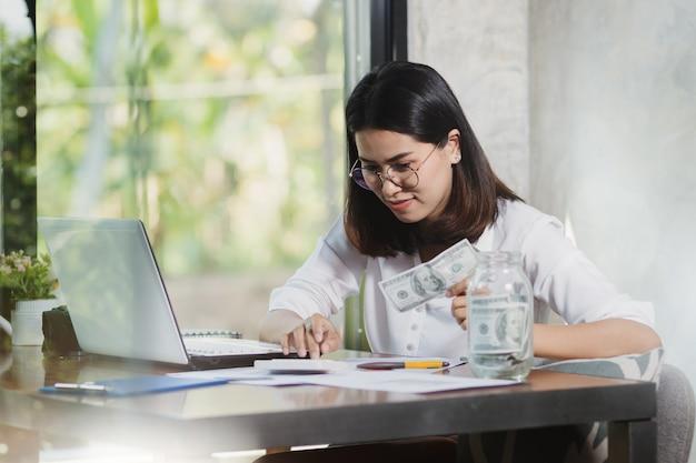 Funzionamento asiatico della donna, contante soldi con felice in ufficio, casa.