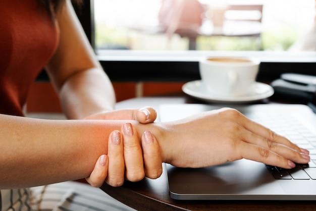 Funzionamento del computer portatile di uso prolungato di dolore della mano del braccio della donna del polso. concetto di assistenza sanitaria e medicina sindrome dell'ufficio