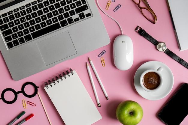 Funzionamento dello spazio di lavoro freelance concept vista superiore sopra il computer portatile piatto. sfondo rosa.