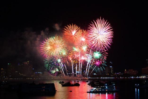 Fuochi d'artificio arcobaleno finale sulla spiaggia e il colore di riflessione sulla superficie dell'acqua