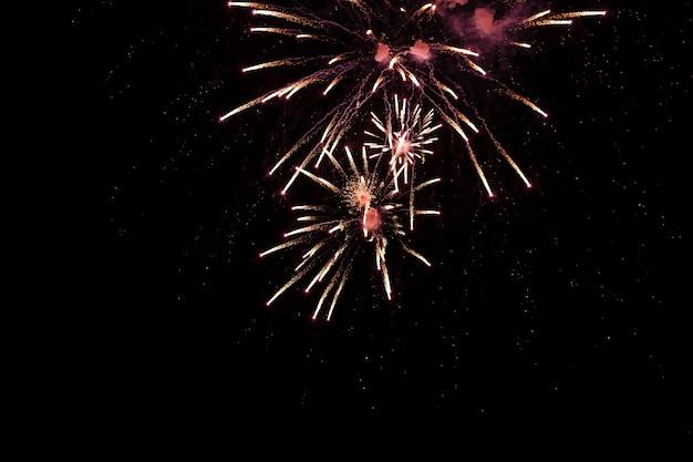 Fuochi d'artificio brillantemente colorati e saluto di vari colori sullo sfondo del cielo notturno. messa a fuoco selettiva