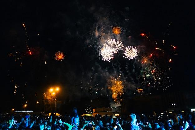 Fuochi d'artificio colorati nel cielo notturno e folla al concerto di kineshma