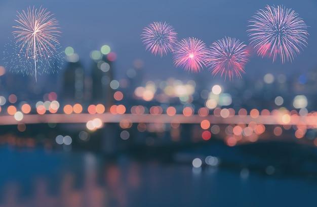 Fuochi d'artificio colorati su luci della città bokeh sfocato