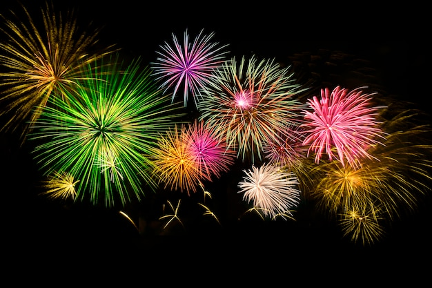Fuochi d'artificio colorati su sfondo cielo di mezzanotte.
