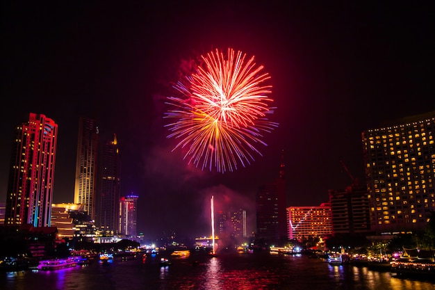 Fuochi d'artificio colorato su sfondo di vista città di notte per il festival di celebrazione.