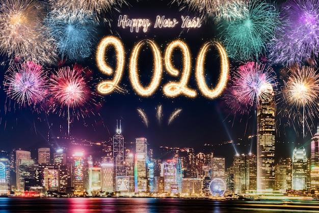 Fuochi d'artificio del buon anno 2020 sopra paesaggio urbano che costruisce vicino al mare alla celebrazione di notte