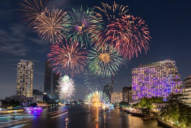 Fuochi d'artificio di capodanno a mezzanotte sopra la città di fiume che circonda con alberghi, ristoranti
