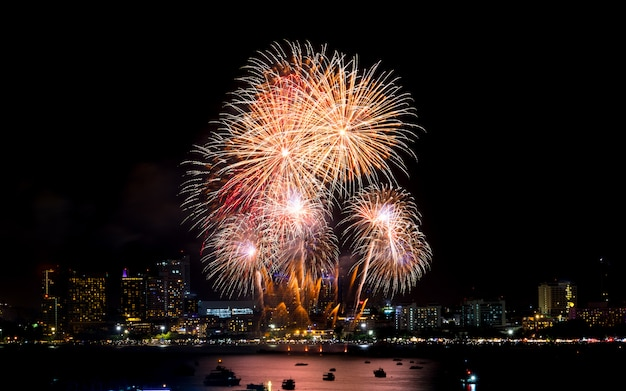 Fuochi d'artificio di felice anno nuovo sopra paesaggio urbano di notte. festa celebrazione festa