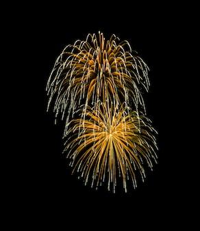 Fuochi d'artificio esplosi dorati isolati su fondo nero
