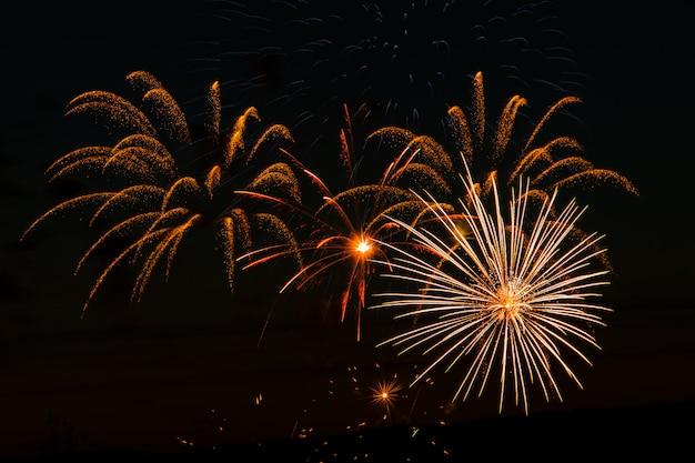 Fuochi d'artificio festivi nel cielo notturno. saluto multicolore luminoso su uno spazio nero. posto per il testo.