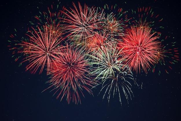 Fuochi d'artificio giallo verde rosso scintillante sopra il cielo stellato