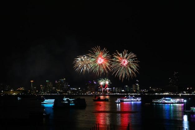 Fuochi d'artificio rossi dell'oro verde sulla spiaggia e sulla riflessione sulla superficie dell'acqua
