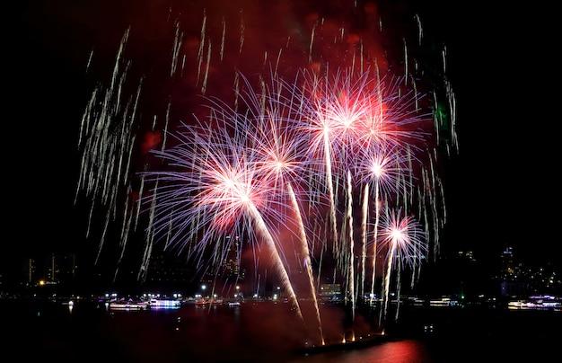 Fuochi d'artificio rossi e viola che spruzzano nel cielo notturno