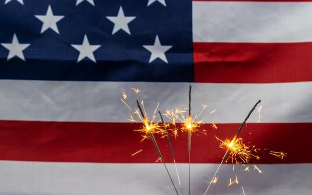 Fuochi d'artificio scintillanti celebrativi sullo sfondo della bandiera degli stati uniti