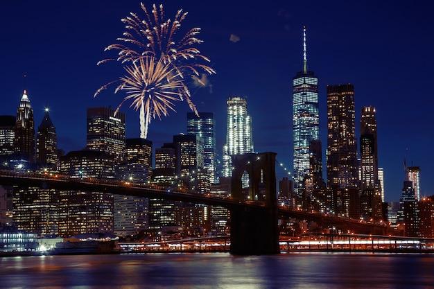 Fuochi d'artificio sopra l'orizzonte di new york city e il ponte di brooklyn