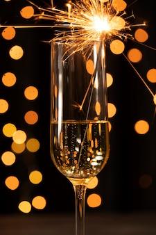 Fuochi d'artificio sulla cima di vetro con champagne