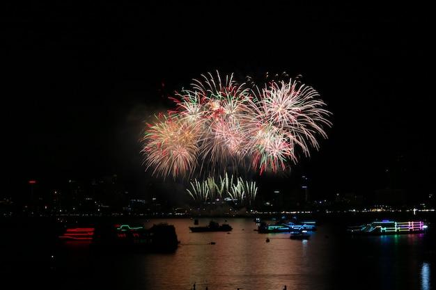 Fuochi d'artificio variopinti della coda corta sulla spiaggia e sulla riflessione sulla superficie dell'acqua