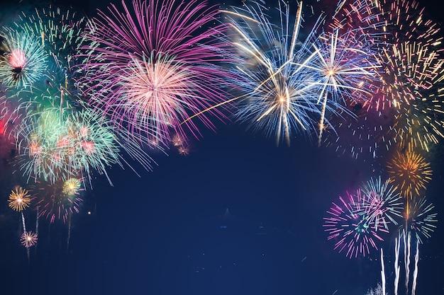 Fuochi d'artificio variopinti sul fondo del cielo nero sopra-acqua